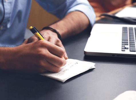 Jeune homme qui prend des notes sur du papier