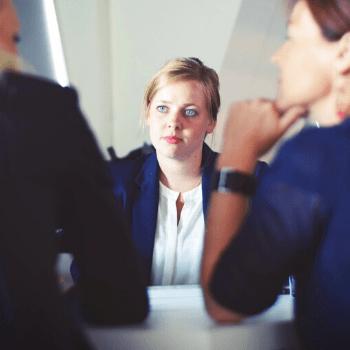 Femme studieuse qui écouter sa direction pendant une réunion professionnelle