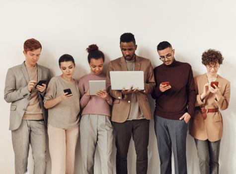 Groupe d'étudiants qui se forme à la vente multicanal à l'aide de leurs smartphones
