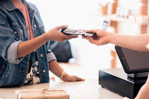 Une commerçante qui tend son TPE à une cliente pour effectuer un paiement par carte bancaire
