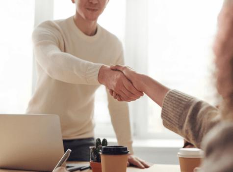 Jeune homme qui serre la main à un dirigeant d'entreprise