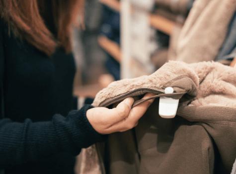 Vendeuse qui range des produits textiles dans un rayon