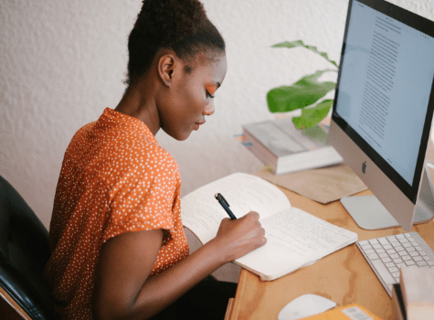 Jeune femme qui prend des notes papiers depuis son ordinateur